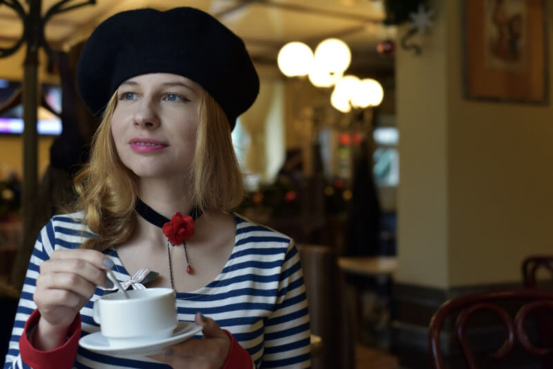 A girl with French hat drinking coffee