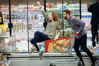 Man and woman having fun while shopping at the supermarket